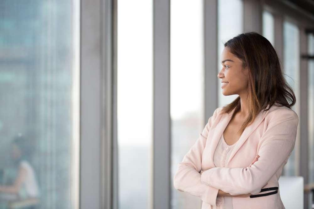 Mulher sorridente com traje corporativo que escolheu uma das carreiras do futuro e se inseriu no mercado de trabalho